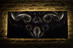 Sinister picture with elements of bas-relief. A picture consisting of two parts, a background and a product, with a diode illumination, and hung on a brick wall royalty free stock image