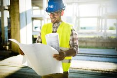 Picture of construction site engineer looking at plan Stock Image