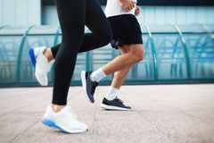 Picture of couple running together in urban area Stock Photo