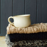 Picture of cozy sweaters and cup of coffee or tea over grey back Stock Photography