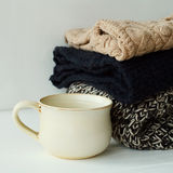 Picture of cozy sweaters and cup of coffee or tea over white bac Stock Photo