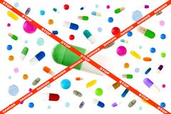 Picture crossing through stop and danger on red ribbon, Symbol image of drugs danger : Many colorful medicines. Pills stock photography