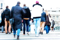 Crowds of people in motion blur crossing a city street Royalty Free Stock Photos