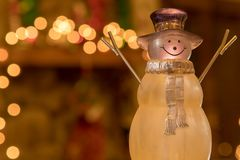 Crystal Holiday Snowman Ornament Sitting in Front of a Decorated Fireplace Mantle. Picture of a crystal snowman ornament sitting in front of a Christmas time stock image