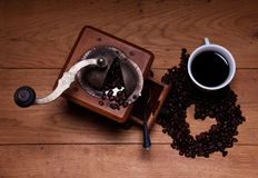 A picture of a cup of coffee and coffee grinder. On a wooden table Royalty Free Stock Images