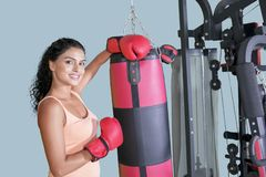 Curly hair woman leaning on boxing bag royalty free stock image