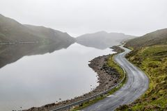 Curving Mountain Lake road. This is a picture of a curving mountain lake road in the morning mist. This lake is called Lake Salt and is located in Donegal royalty free stock images