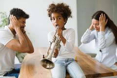 Picture of child making noise by playing trumpet Stock Photo