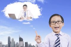 Cute boy imagining to be a doctor. Picture of cute little boy imagining his dream while pointing at a doctor on a cloud bubble Stock Image