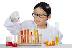 Little boy mixing a chemist liquid on studio. Picture of cute little boy mixing a chemist liquid, isolated on white background Stock Photo