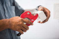Picture of cutting metal-plastic by special red scissors. Royalty Free Stock Photography