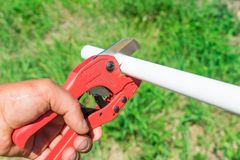 Picture of cutting plastic pipe by special red scissors stock images