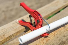 Picture of cutting plastic pipe by special red scissors stock photos