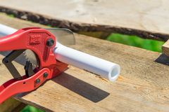 Picture of cutting plastic pipe by special red scissors.  stock photos