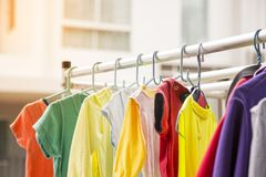 This picture depicts a colorful baby shirt hanging on an outdoor clothes rack. Stock Photography