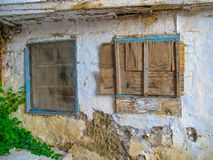Derelict house with boarded up window. This is a picture of a derelict house with a boarded up window, crumbling plaster and flaking paint stock image
