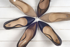 A picture of different shoes, Shot of several types of shoes, Several designs of women shoes. Leather Shoe, Sport Shoe. Pile of v. Arious female shoes on wooden royalty free stock photo