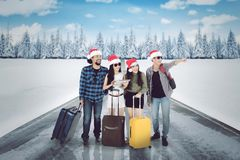 Diversity tourists with suitcase on the snowy road royalty free stock images
