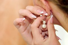 Picture earrings on the ear. The bride wears a stock photos
