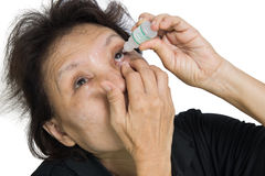 A picture of an elderly woman applying eye-drops over white back Royalty Free Stock Images