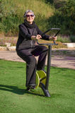Picture of elderly woman working out on a spinning cycle trainer Stock Photos