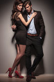 Picture of a elegant couple embracing. Fulll length picture of a elegant couple embracing. The men is leaning on a dark grey wall with one hand in his pocket Royalty Free Stock Photos