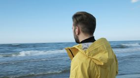 The tourist man walking on the lonely beach. The picture of enjoyment adult stylish hipster in coat walk on the wild empty seaboard close up. Sunny cloudy stock video
