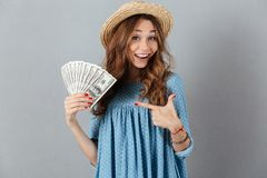Excited young cheerful woman holding money. Picture of excited young cheerful woman standing over grey wall wearing hat holding money. Looking camera pointing Stock Photo