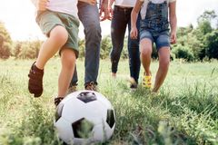A picture of familie`s legs waking on meadow`s grass. They are playing football. There is a ball for game in front of