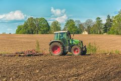 Picture of farmer plowing stubble field stock photography