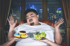 Fat man choosing foods with confused expression stock photos