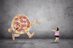 Tasty pizza chasing fat woman royalty free stock images