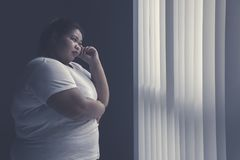 Fat woman thinking something by the window royalty free stock photo