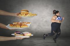 Fat woman escaping from unhealthy foods. Picture of fat women looks scared while escaping from unhealthy foods offered. Diet concept royalty free stock photos