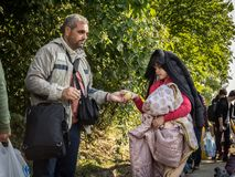 Two refugees, father and daughter, exchanging food on Croatia Serbia border, between the cities of Bapska & Berkasovo. Picture of a father and his daughter, both stock photography