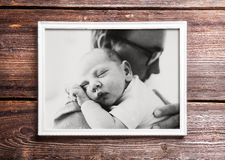 Picture of father holding his baby. Wooden background. royalty free stock photography