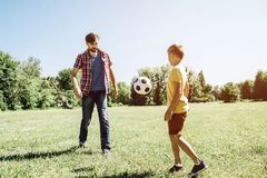 A picture of father nd son playing football game. THere is a ball flying from dad to son. It is in air. It is sunny. Outside on field stock images