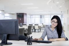 Female entrepreneur smiling at the camera. Picture of female entrepreneur smiling at the camera while working with a computer in the office Royalty Free Stock Photography