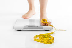 A picture of female feet standing on a bathroom scales and a tap Stock Photo