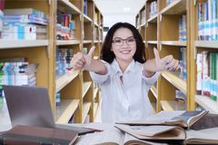 Female high school student with thumbs up. Picture of female high school student showing thumbs up while studying in the library Royalty Free Stock Photos