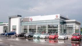 Picture of Fiat dealer salon with cars outside of it. There are cars with different colors of body. It is cloudy outide royalty free stock image