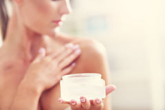 Picture of a fit woman holding lotion over her body Royalty Free Stock Photos