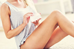 Picture of a fit woman holding lotion over her legs. Picture showing fit woman holding lotion over her legs Royalty Free Stock Image