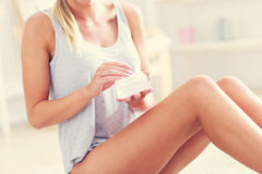 Picture of a fit woman holding lotion over her legs. Picture showing fit woman holding lotion over her legs Stock Image