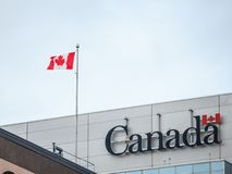 Canada Wordmark, the official logo of the Canadian government, on an administrative building next to a Canadian flag waiving stock photo