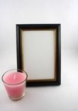 Picture Frame. A picture frame with a pink candle in front of it Royalty Free Stock Photo