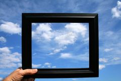 Picture Frame. A person holding up a picture frame against a beautiful blue sky full of clouds Royalty Free Stock Images