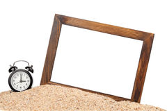 Picture frame and alarm clock on the beach. Wooden picture frame and alarm clock on the beach Royalty Free Stock Photos