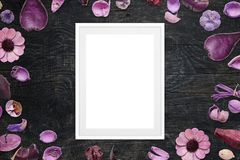 Picture frame on black wooden desk surrounded with purple floral decorations.  Stock Photography