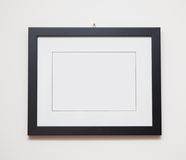 Picture frame. Blank black picture frame on white wall Royalty Free Stock Photo
